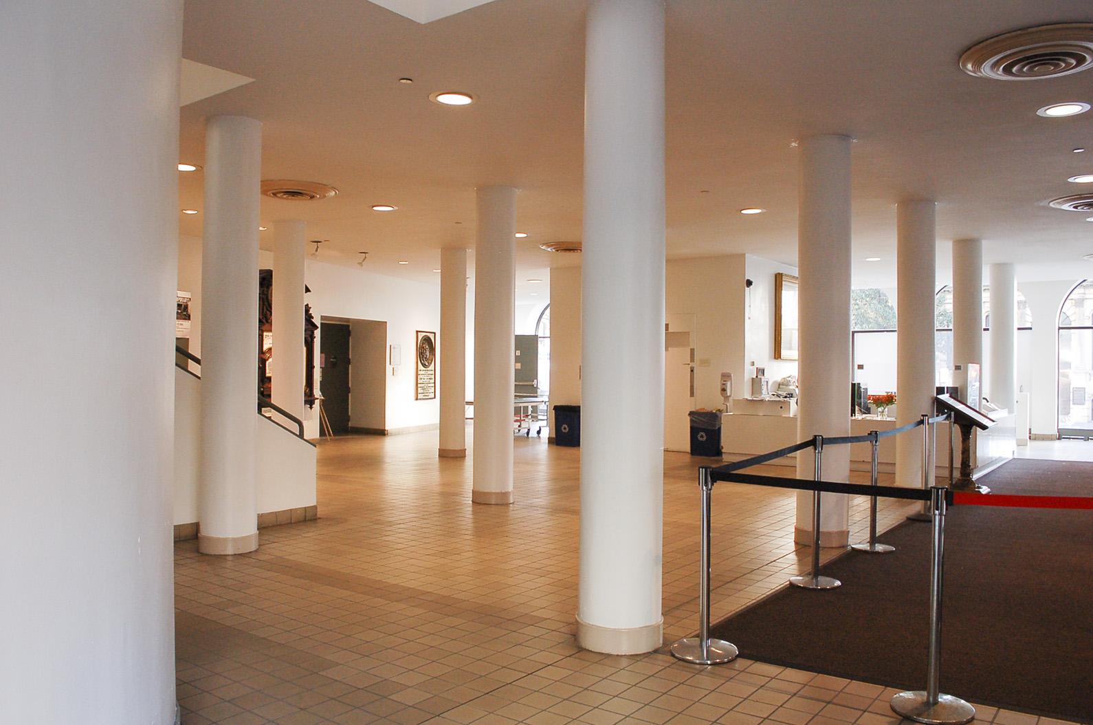 Fotografía desde la esquina suroeste de la planta baja del vestíbulo de la Cooper Union. En primer plano está la curva del cilindro del elevador.